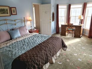 King bed with iron headboard and a solid wood desk in a bay window