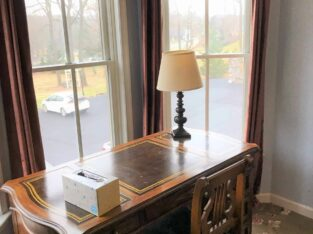 A solid wood desk in a bay window with a lamp and brown curtains